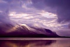 Landskap. Berg och sjö i mist i morgon med den purpurfärgade sänkan Royaltyfri Foto