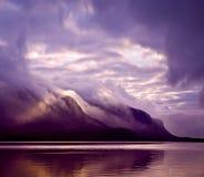 Landskap Berg och sjön i mist i morgon med lilor färgar Arkivfoto