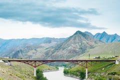 Landskap bron, berget, floden och himmel Arkivfoton