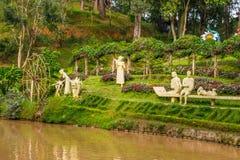 Landskap designen av kopplar av den tropiska trädgården med statyer på en flodsida Royaltyfria Bilder