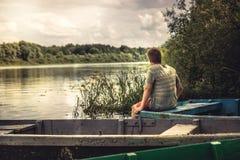 Landskap för bygd för begrundande för tonåringpojke ensamt på flodfartyget under bygdsommarferier fotografering för bildbyråer