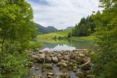 Landskap för en klar bergsjö - dal med en liten vattenfall Royaltyfri Bild