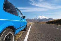 Landskap för högt berg med en blå bil på vägrenen norr panorama för caucasus liggandeberg Royaltyfri Fotografi