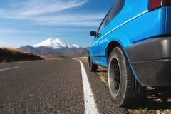Landskap för högt berg med en blå bil på vägrenen norr panorama för caucasus liggandeberg Arkivbild
