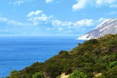 Landskap för havskust - gröna berg på den blåa bakgrunden för molnig himmel Arkivfoton