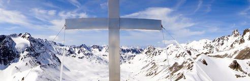 Landskap för panoramavinterberg med ett kors för silveraluminiumtoppmöte i mitt i förgrunden royaltyfri bild