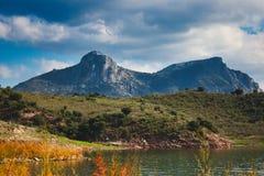 Landskap för stenigt berg ovanför en fridfull sjö på Zahara de la Toppig bergskedja, Anadalucia fotografering för bildbyråer