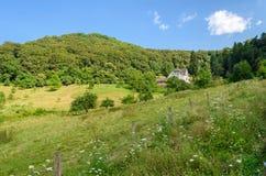 Landskap för Tysklandsommarland med ängen, skogen och ett hus, bakgrund Royaltyfri Bild