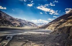 Landskap fotoet av den bergfloder och vägen för blåa himlar med skuggor fotografering för bildbyråer