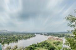 Landskap från kullen bredvid floden, flyttande moln, träd Fotografering för Bildbyråer