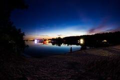 Landskap Härlig färgrik solnedgång med sikt av sjö- och skogljus av musikfestivalen Royaltyfria Foton