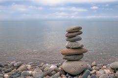 Landskap, hav, himmel, stenig strand och pyramid av lägenhetgrå färgstenar arkivfoton