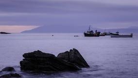 Landskap i Skottland - fartyg, stenar, sjö och kullar Royaltyfri Bild