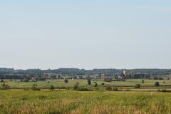 Landskap i sommar med blå himmel och moln med den ljusa solen i bakgrunden arkivbild