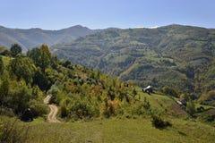 Landskap landsvägen och bergbyn i början av hösten Arkivfoto