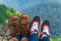 Landskap lopp, turism Ett par av fot i skorna mot bakgrunden av bergen Horisontal inrama Arkivbild
