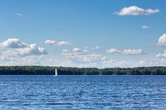 Landskap med den härliga sjön och segelbåten Royaltyfri Foto