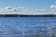Landskap med den härliga sjön och segelbåten Arkivfoto
