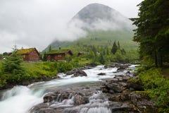 Landskap med den trähus, floden och berget, Norge Royaltyfri Foto
