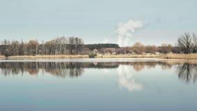 Landskap med det enorma rökiga molnet på horisont Damm vass runt om sjön, solig våratmosfär lager videofilmer
