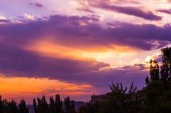 Landskap med dramatiskt ljus - härlig guld- solnedgång med genomdränkt himmel och moln royaltyfri bild