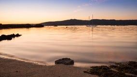 landskap med en segelbåtsegling på solnedgången på kusterna av en ö Galicia arkivbild
