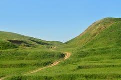 Landskap med en trampad bana som passerar till och med en underbar grön bergig terräng Foto av härligt landskap lättnadsutrymme Royaltyfri Fotografi