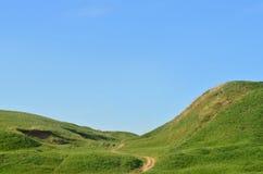 Landskap med en trampad bana som passerar till och med en underbar grön bergig terräng Foto av härligt landskap lättnadsutrymme Royaltyfri Bild