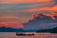 Landskap med ett fartyg som svävar på vattnet På bakgrunden av konturen av shorelinen och en brännhet solnedgång close upp royaltyfri bild