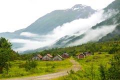 Landskap med gamla trähus och berg som täckas av moln, Norge Royaltyfria Bilder