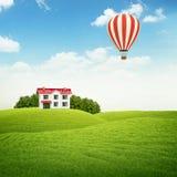 Landskap med gräsmatta med hus- och luftballongen i himmel Royaltyfria Bilder