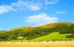 Landskap med gröna kullar, blå himmel, huset och djur på sparat fotografering för bildbyråer