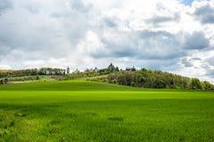 Landskap med grönt gräs, träd och kloster upp kullen under molnig himmel arkivbild