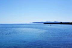 Landskap med havet, berg och att stå upp skovlar royaltyfria bilder