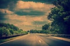 Landskap med huvudväg- och vindturbiner Arkivbilder