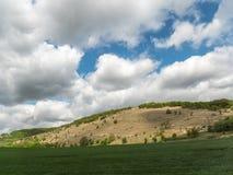 Landskap med ?kerbruka f?lt och gr?nomr?den p? en Sunny Day med molnig himmel royaltyfri bild