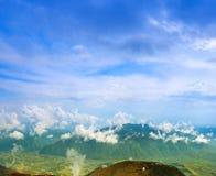 Landskap med moln, berg, blå himmel och byn. Carpathi Arkivfoto