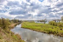 Landskap med molnig himmel, floden, fältet och kyrkan Royaltyfri Bild
