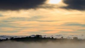 Landskap med solinställningen bak moln och dimma Arkivbilder