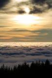 Landskap med solinställningen bak moln och dimma Royaltyfri Fotografi