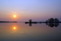 Landskap med spegelreflexion i fjärden på floden på solnedgången Arkivbilder