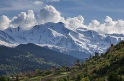 Landskap med Svan watchtowers och jordbruks- fält på bakgrunden av snö-korkade bergmaxima och moln, Svaneti Royaltyfria Bilder