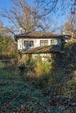 Landskap med träbron och det gamla huset i by av Bozhentsi, Bulgarien Royaltyfri Foto