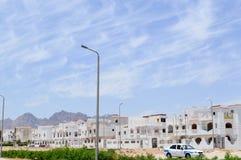Landskap med vita små fyrkantiga hus, stugor och radhus på den arabiska muslimska islamiska gatan i Egypten mot en blå himmel in royaltyfria bilder