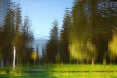 Landskap reflekterat i vatten mot bakgrund field blåa oklarheter för grön vitt wispy natursky för gräs arkivfoton