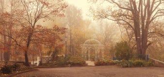 Landskap romantisk gazebo i parkera i morgondimman sent arkivfoton