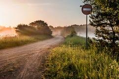 Landskap, solig gryning med vägen och vägmärke Royaltyfri Bild
