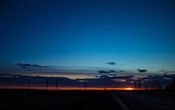 Landskap solnedgången över vägen och fältet Bilen på vägen Bakgrund royaltyfri fotografi