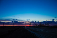 Landskap solnedgången över vägen och fältet Bilen på vägen Bakgrund arkivbild