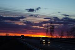 Landskap solnedgången över vägen och fältet Bilen på vägen Bakgrund arkivfoto